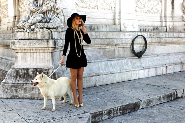 A model holds a dog by a leash as she waits for her turn to enter the catwalk during the recording of a Portuguese soap opera at Lisbon's Restauradores Square, on January 11, 2014. (Photo by Francisco Seco/Associated Press)