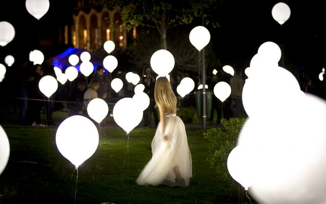 A woman walks between balloons part of an art light installation in Bucharest, Romania, Thursday night, April 23, 2015. Bucharest hosts the Spotlight International Light Festival for the next three days. (Photo by Vadim Ghirda/AP Photo)