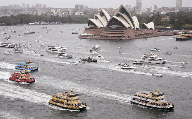 Competitors in the annual ferry boat race are supported by a spectator flotilla as they cruise past the Sydney Opera House as part of Australia Day celebrations in Sydney, Thursday, January 26, 2017. (Photo by Rick Rycroft/AP Photo)