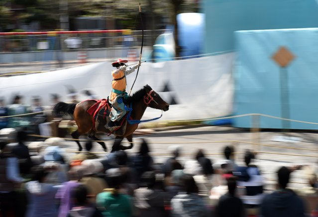 An archer wearing ancient samurai warrior dress shoots an arrow towards the target while riding on horseback during a Yabusame demonstration of the 13th-century samurai martial arts in Tokyo on April 18, 2015. (Photo by Toshifumi Kitamura/AFP Photo)