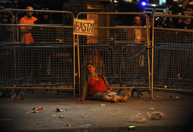 "An injured woman lies on the street during a demonstration organized by Spain's ""indignant"" protesters to decry an economic crisis they say has ""kidnapped"" democracy, on September 25, 2012 in Madrid. (Photo by Dominique Faget/AFP Photo)"
