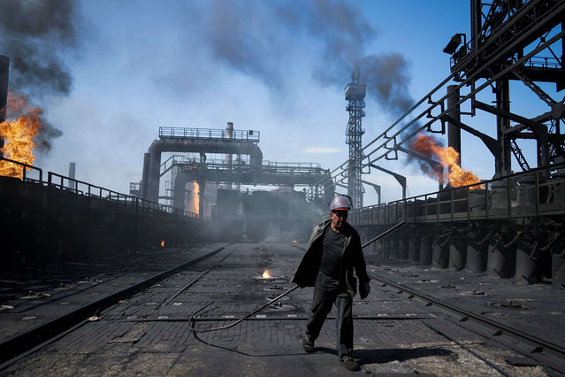 In this Tuesday, August 4, 2015 file photo a worker carries a metal rod at the front-line Avdiivka coking plant in eastern Ukraine. Fighting between government troops and separatist rebels in eastern Ukraine escalated on Tuesday, January 31, 2017, killing several people overnight, injuring many more and trapping 200 coalminers underground, the warring sides reported. (Photo by Mstyslav Chernov/AP Photo)
