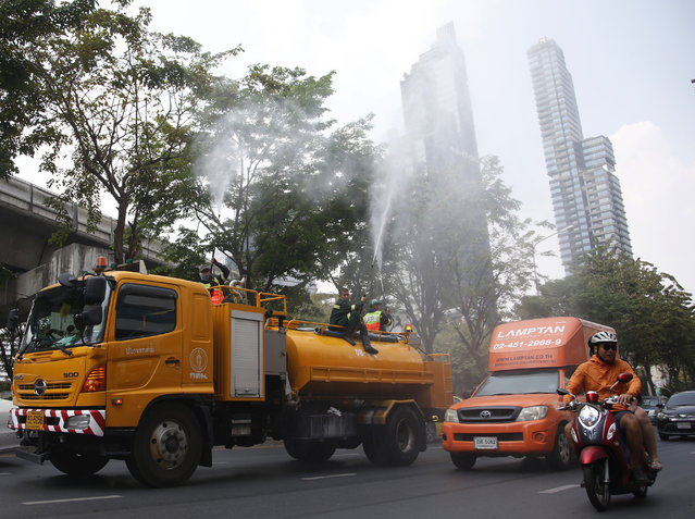 Bangkok toad crews spray water in hopes to control some of the smog in Bangkok, Thailand, Monday, January 14, 2019. Unusually high levels of smog worsened by weather patterns are raising alarm across Asia. (Photo by Sakchai Lalit/AP Photo)