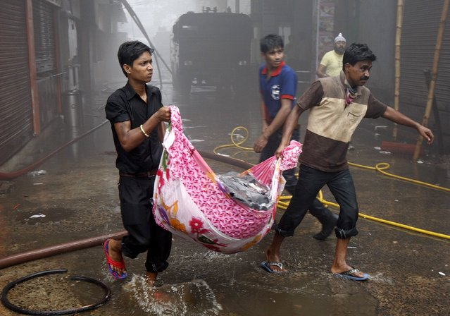 People carry their goods to a safer place after a fire broke out in a shopping mall in Kolkata, India, April 26, 2015. (Photo by Rupak De Chowdhuri/Reuters)