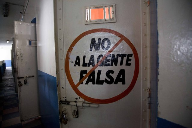 """This April 16, 2015 photo shows the exterior of a cell door covered with the message in Spanish: """"No to fake people"""" at the now empty Garcia Moreno Prison, during a guided tour for the public in Quito, Ecuador. Rich and poor, good and bad, innocent and guilty, inmates used the walls to record their days. (Photo by Dolores Ochoa/AP Photo)"""
