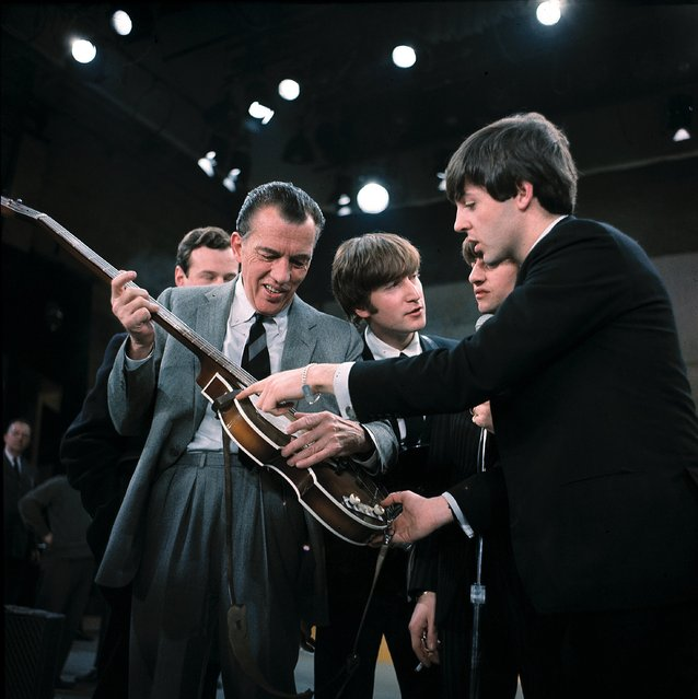 "In this February 9, 1964. file photo Paul McCartney, right, shows his bass guitar to Ed Sullivan before the Beatles' live television appearance on ""The Ed Sullivan Show"" in New York along with John Lennon, center, and Ringo Starr, behind McCartney, and Beatles manage Brian Epstein, behind Sullivan. (Photo by AP Photo)"
