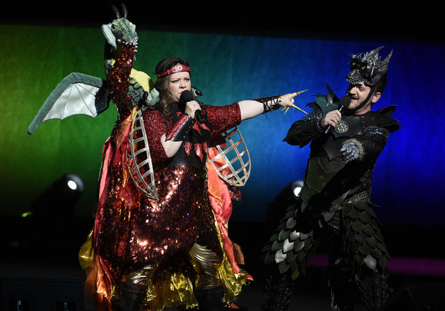 """Melissa McCarthy, left, a cast member in the upcoming film """"Superintelligence"""", and her husband Ben Falcone, the film's director, arrive onstage in costume during the Warner Bros. presentation at CinemaCon 2019, the official convention of the National Association of Theatre Owners (NATO) at Caesars Palace, Tuesday, April 2, 2019, in Las Vegas. (Photo by Chris Pizzello/Invision/AP Photo)"""
