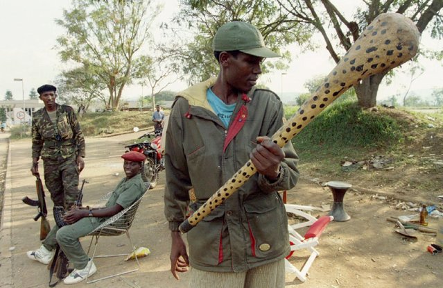 A Rwandan Patriotic Front rebel observes a nail-spiked club found near a militia checkpoint which was abandoned after the rebel victory in Kigali, Rwanda July 7, 1994. The genocide lasted around 100 days and stopped after rebels fought their way to the capital, led by Paul Kagame, Rwanda's current president. (Photo by Corinne Dufka/Reuters)