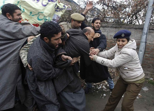 An Indian policewoman tries to detain Kashmiri lawmaker Sheikh Abdul Rashid (C), president of Awami Ittihad Party (AIP), a pro-India party, along with supporters during a protest in Srinagar February 9, 2014. Authorities imposed restrictions across Srinagar as separatists called for a three-day shutdown to demand for the remains of Mohammad Afzal Guru, a Kashmiri man who was executed on February 9, 2013, for an attack on India's parliament in 2001, local media reported on Sunday. (Photo by Danish Ismail/Reuters)