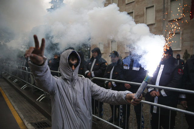 A protester gestures as he holds a flare in front of a police formation during an anti-government rally in Tirana, Albania, Saturday, April 13, 2019. Albanian opposition parties have gathered supporters calling for the government's resignation and an early parliamentary election. (Photo by Visar Kryeziu/AP Photo)