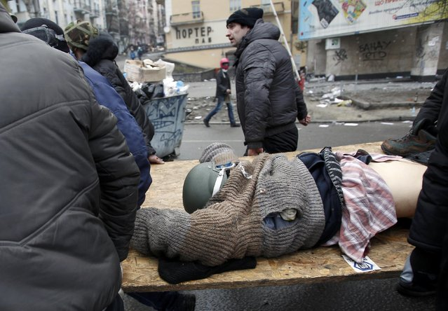 Anti-government protesters carry an injured man on a stretcher after violence erupted in the Independence Square in Kiev February 20, 2014. (Photo by David Mdzinarishvili/Reuters)