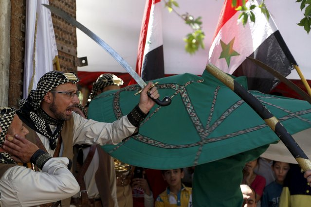 A man dances with a sword at a traditional music event organized by the Ministry of Tourism in Damascus May 2, 2015. (Photo by Omar Sanadiki/Reuters)