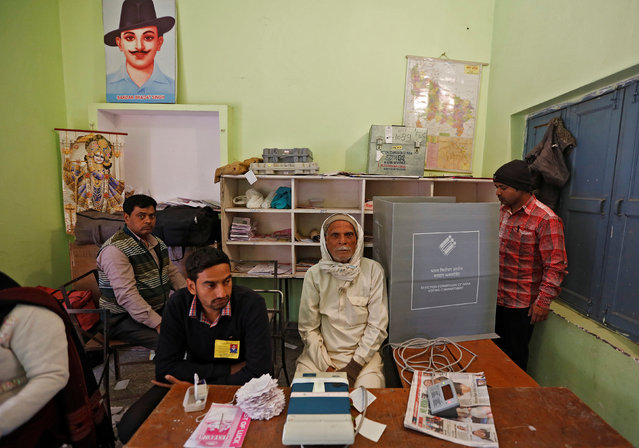 A man (R) casts his vote as polling officers look on at a polling booth during the state assembly election in Hapur, in the central state of Uttar Pradesh, India, February 11, 2017. (Photo by Adnan Abidi/Reuters)