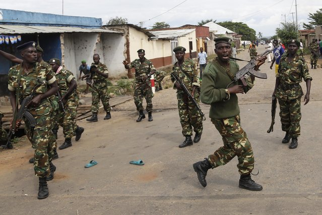 Soldiers disperse a crowd by firing into the air after demonstrators cornered Jean Claude Niyonzima a suspected member of the ruling party's Imbonerakure youth militia in a sewer in the Cibitoke district of Bujumbura, Burundi, Thursday May 7, 2015. (Photo by Jerome Delay/AP Photo)