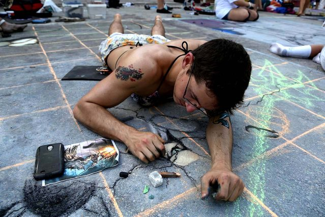 Troy Ferguson, of Lake Worth High school, chalks the pavement. (Photo by Greg Lovett/The Palm Beach Post)
