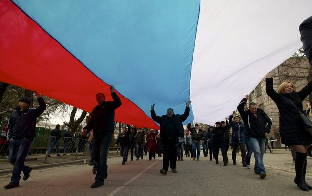 Local residents carry a Russian flag and shout slogans rallying over the streets of Crimean capital Simferopol, Ukraine, on Saturday, March 1, 2014. (Photo by Ivan Sekretarev/AP Photo)