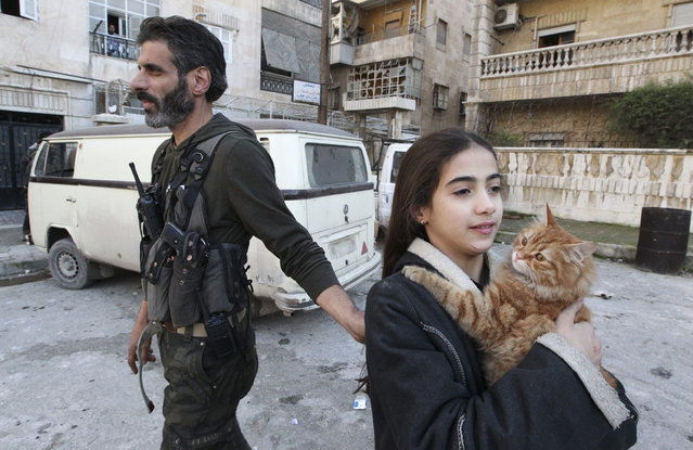 """A """"Free Syrian Army"""" fighter stands next to his daughter as she holds a cat in Aleppo's Izaa district, Syria December 30, 2012. (Photo by Muzaffar Salman/Reuters)"""