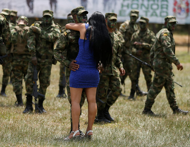 A Colombian soldier hugs his girlfriend during the graduation ceremony of soldiers in Nilo, Colombia, February 17, 2017. The soldiers will be deployed to occupy territories formerly controlled by FARC rebels. (Photo by Jaime Saldarriaga/Reuters)