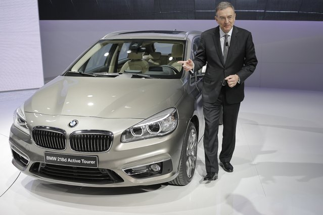 Dr. Norbert Reithofer, CEO of BMW, poses in front of the new BMW 218d Active Tourer during the media day of the 84th Geneva International Motor Show, Switzerland, Tuesday, March 4, 2014. (Photo by Laurent Cipriani/AP Photo)