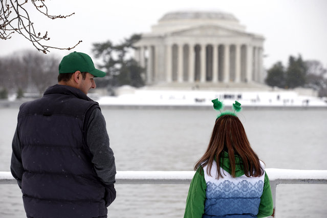 Craig Hyatt, left, and his wife Shannon Hyatt, both from Toronto, look toward the Jefferson Memorial after a St. Patrick's Day winter storm, Monday, March 17, 2014 in Washington. Snow has been falling in parts of the Mid-Atlantic and Northeast as winter-weary motorists faced another potentially treacherous commute Monday morning, just days before the start of spring. (Photo by Alex Brandon/AP Photo)