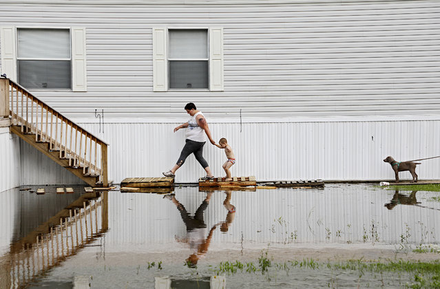 Samantha Karnes and her son Anthony Pickett, 3, walk up to their neighbor's mobile home to check on him as floodwater from the Arkansas River approaches at the Riverside Mobile Home Park in Muskogee, Okla., Wednesday, May 22, 2019. (Photo by Mike Simons/Tulsa World via AP Photo)