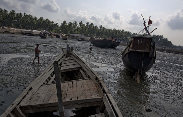 In this Wednesday, May 13, 2015 photo fishing boats belong to Rohingiya Muslims lay-on the foreshore during law-tide in Thay Chaung harbor, north of Sittwe, western Rakhine state, Myanmar. (Photo by Gemunu Amarasinghe/AP Photo)