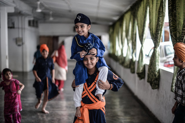 An ethnic Malaysian Sikh boy carries his brother as they play during the Vaisakhi Festival, or the Sikh New Year Festival, at Gurdwara Sahib temple in Kuala Lumpur on April 14, 2016. The Vaisakhi Festival is the most important event in the Sikh calendar and celebrates the birth of Khalsa. (Photo by Mohd Rasfan/AFP Photo)