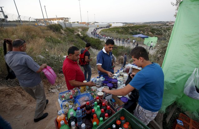 Palestinian labourers buy food supplies before they cross into Israel through Hashmonaim checkpoint near the West Bank village of Nilin, west of Ramallah May 25, 2015. (Photo by Mohamad Torokman/Reuters)