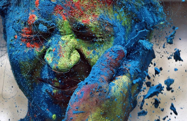 A man smears the face of a woman with colors during celebrations marking Holi, the Hindu festival of colors, in Mumbai, India, Monday, March 17, 2014. The holiday, celebrated mainly in India and Nepal, marks the beginning of spring and the triumph of good over evil. (Photo by Rajanish Kakade/AP Photo)