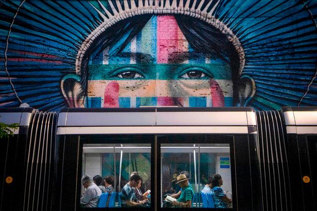 Commuters ride past the mural called Ethnicity, made by Brazilian graffiti artist Eduardo Kobra, in Rio de Janeiro, Brazil, on June 13, 2019. (Photo by Mauro Pimentel/AFP Photo)