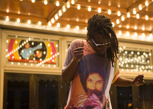 A woman dances during a candle light vigil in remembrance to Prince outside the Warner Theatre in Washington, DC on April 21, 2016. (Photo by Andrew Caballero-Reynolds/AFP Photo)
