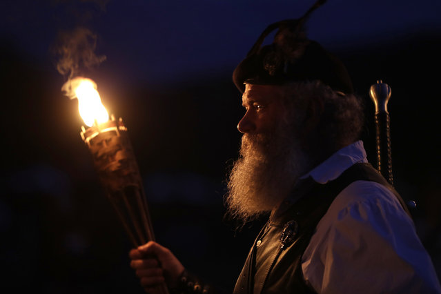 Al Thompson, of Milan, Ind., waits to announce his clan's arrival during the opening torchlight service to begin the 64th annual Grandfather Mountain Highland Games at MacRae Meadows in Linville, N.C., Thursday, July 11, 2019. The games celebrate the history and culture of Scottish people in North Carolina. (Photo by Chuck Burton/AP Photo)