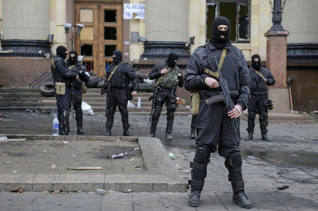 """Armed men in masks, representing Ukrainian special forces, stand guard outside the regional administration building in Kharkiv, April 8, 2014. Ukraine has launched an """"anti-terrorist"""" operation in the eastern city of Kharkiv and about 70 """"separatists"""" have been arrested for seizing the regional administration building, Ukrainian Interior Minister Arsen Avakov said on Tuesday. (Photo by Olga Ivashchenko/Reuters)"""