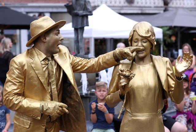 "Artists called ""Golden Wedding"" takes part in the festival ""Statues en Marche"" in Marche-en-Famenne, Belgium, July 20, 2019. (Photo by Yves Herman/Reuters)"