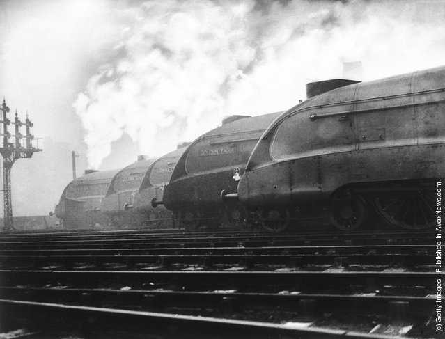 A row of LNER streamlined locomotives belch out smoke at a London railway station, where they are to be tested out
