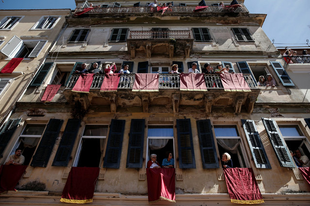 "People watch from their balconies and windows, after participating in the Greek Orthodox Easter tradition of ""Botides"" on Holy Saturday marking the so-called ""First Resurrection"", on the island of Corfu, Greece, April 30, 2016. (Photo by Alkis Konstantinidis/Reuters)"