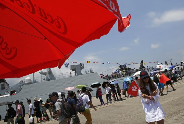 A visitor poses for photos next to a naval ship during the open day of Stonecutter Island navy base of Chinese People's Liberation Army (PLA) in Hong Kong to mark the 18th anniversary of the Hong Kong handover to China in Hong Kong, Wednesday, July 1, 2015. (Photo by Kin Cheung/AP Photo)