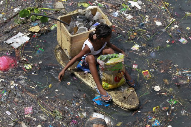 A girl sits on a makeshift styrofoam raft as she collects recyclable material from floating garbage in a polluted river at Navotas city, north of Manila, Philippines July 2, 2015. (Photo by Romeo Ranoco/Reuters)