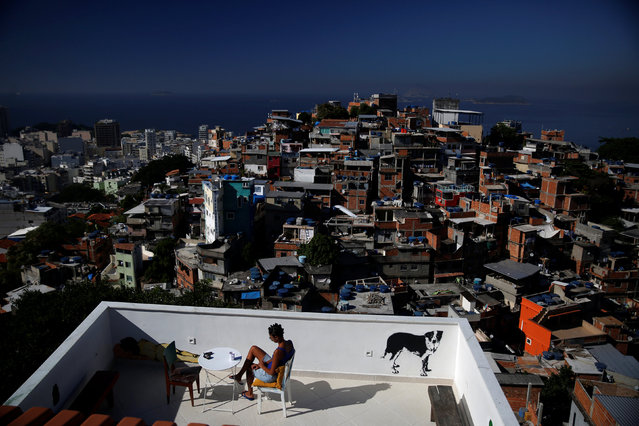 A woman sits on a terrace at Tiki hostel in Cantagalo favela, in Rio de Janeiro, Brazil, April 16, 2016. (Photo by Pilar Olivares/Reuters)