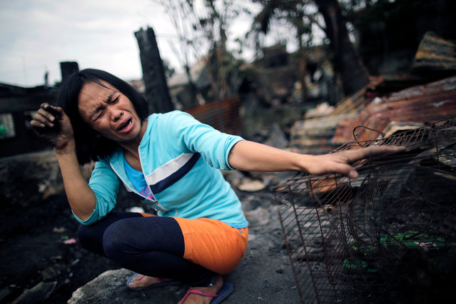 A Filipino informal settler cries next to her burnt home after a fire at a shantytown in Paranaque city, south of Manila, Philippines, 23 February 2019 (issued 13 June 2019). (Photo by Francis R. Malasig/EPA/EFE)