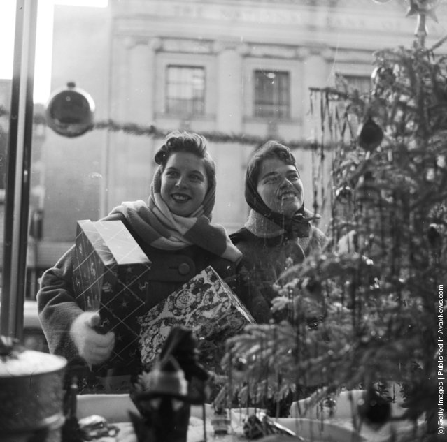 1955: Happy Christmas shoppers happily gaze at the window displays of the shops of Washington DC