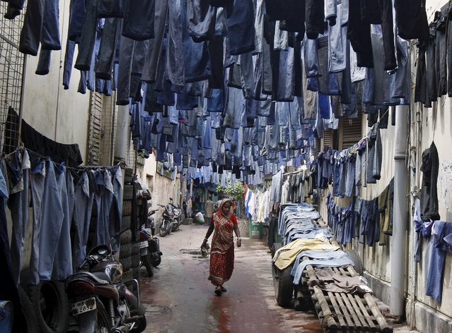 A woman walks through an alley as used pairs of jeans are hung to dry before they are sold in a second-hand clothes market in Kolkata, India, June 29, 2015. (Photo by Rupak De Chowdhuri/Reuters)