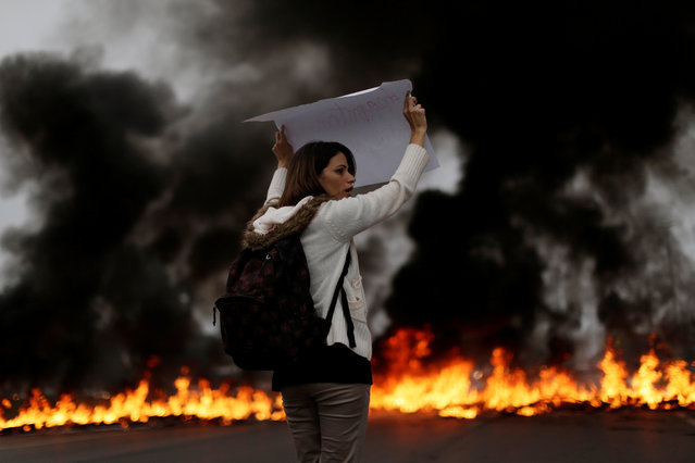 A demonstrators holds a placard in front of a burning barricade during a protest against President Michel Temer's proposal to reform Brazil's social security system in the early hours of general strike in Brasilia, Brazil, April 28, 2017. (Photo by Ueslei Marcelino/Reuters)