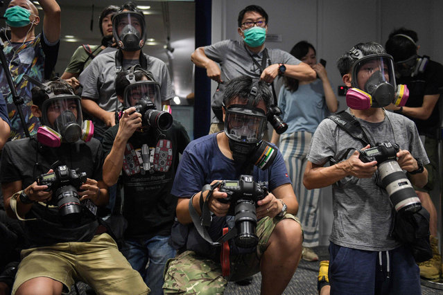 Photojournalists wearing protective masks attend a police press conference in Hong Kong on October 8, 2019. The financial hub has been gripped by four months of rallies, and last weekend saw much of the city grind to a halt as masked demonstrators took to the streets in defiance of a controversial ban on face coverings. (Photo by Nicolas Asfouri/AFP Photo)