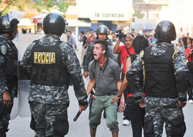 Supporters of the Libertad y Refundacion, LIBRE, political party, shout slogans against the Honduran government during a clashes with police, outside the congress building in Tegucigalpa, Honduras, Tuesday, May 13, 2014. Hundreds of supporters of former President and now Congressman, Manuel Zelaya, clashed with riot police and soldiers after occupying the National Congress building with him. (Photo by Fernando Antonio/AP Photo)