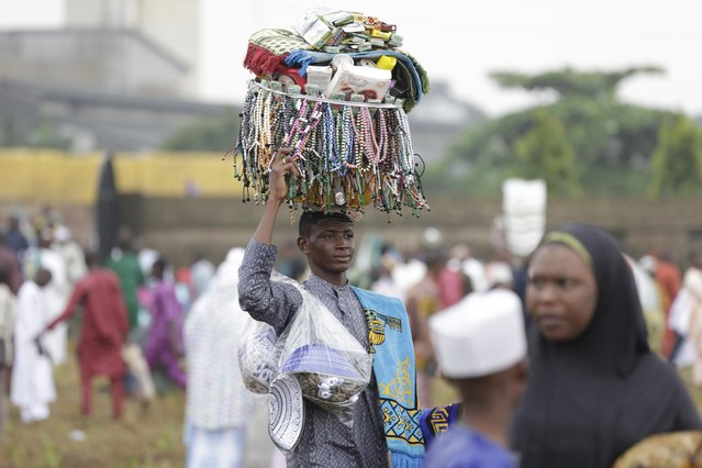 A man sells prayer beads and prayer caps during Eid al-Fitr in Lagos, Nigeria, Friday, July 17, 2015, marking the end of the Muslim holy fasting month of Ramadan. (Photo by Sunday Alamba/AP Photo)