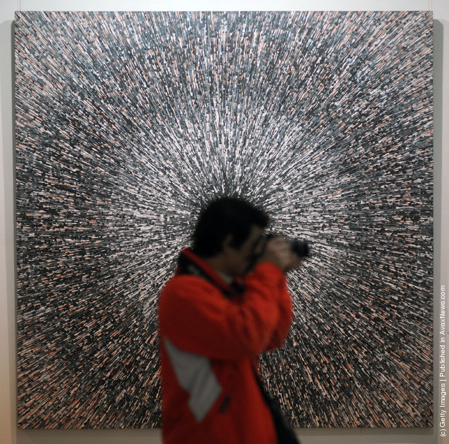 A visitor takes pictures in front of the work entitled 'Universal Speed NO.19' by Chinese artist Meng Luding