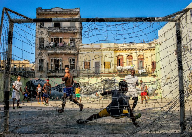 Young men play a heated game of soccer in an urban soccer field in the middle of Old Havana, May 6, 2016. Baseball was traditionally the national sport, but the popularity of soccer is on the rise, particularly with young people. (Photo by Dotan Saguy)