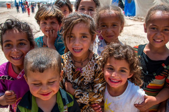 Iraqi children stand at a camp for internationally display people in Hammam al- Alil on May 14, 2017, after fleeing west Mosul due to the government forces ongoing offensive against Islamic State (IS) group jihadists. (Photo by Fadel Senna/AFP Photo)