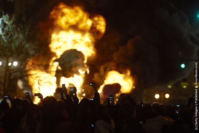 The crowd takes pictures with mobile phones while a combustible 'Ninot' caricatures burns in the background during the last day of the 'Fallas' festival on March 19, 2012 in Valencia